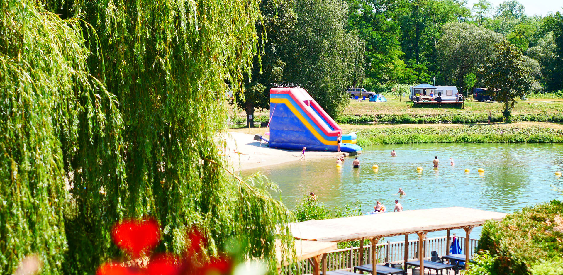 Natural summing lake with water slides and inflatable games at the campsite Les Castors in the Haut-Rhin