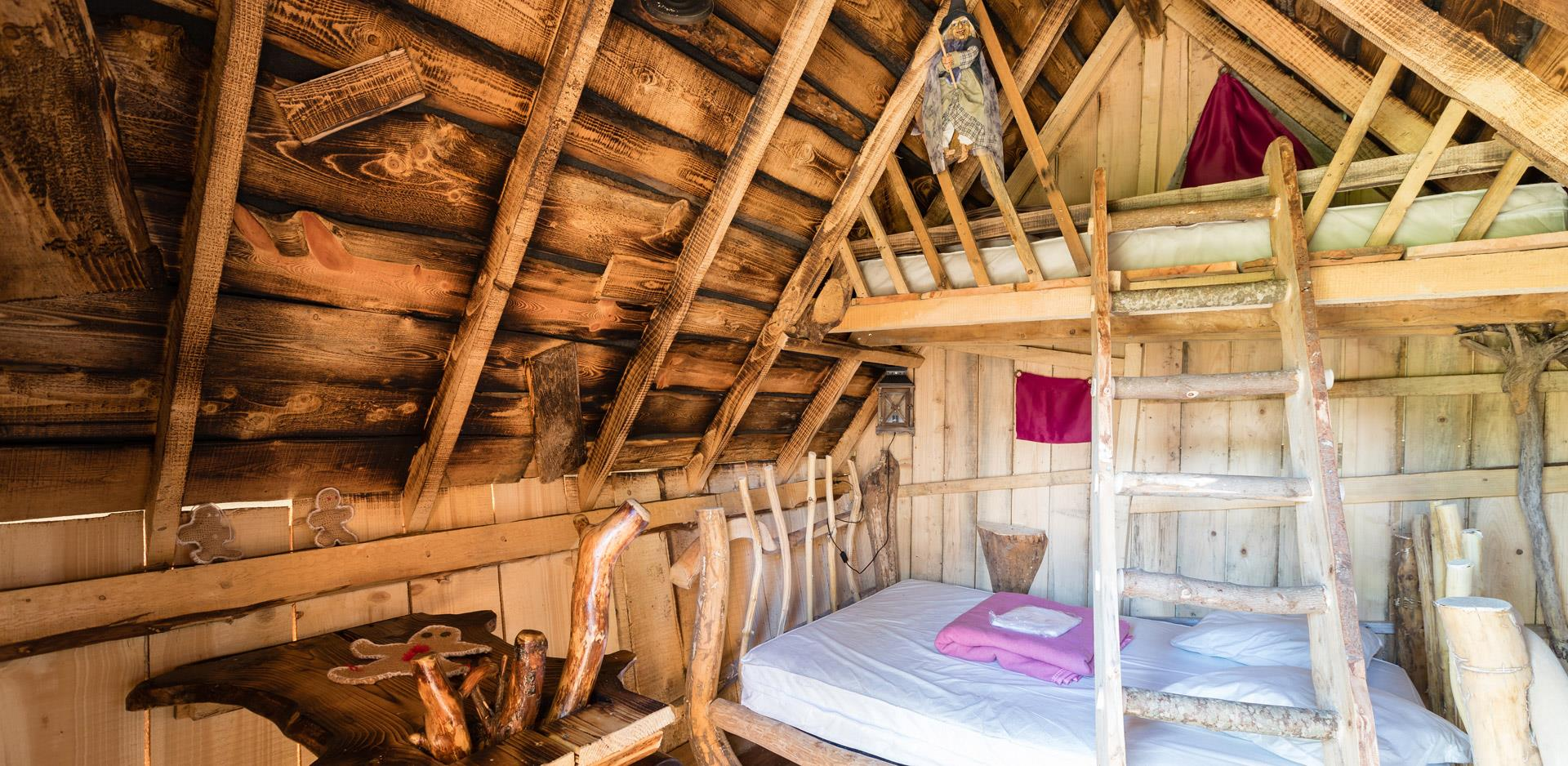 Rental of atypical accommodations near the Vosges Mountains: view of a bedroom area of a wooden cabin