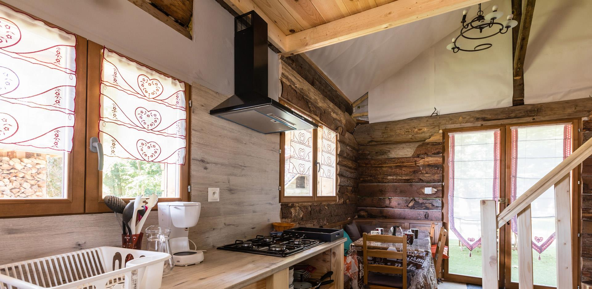 Wooden logs chalet's kitchen, up for rental at the Campsite Les Castors located in Alsace