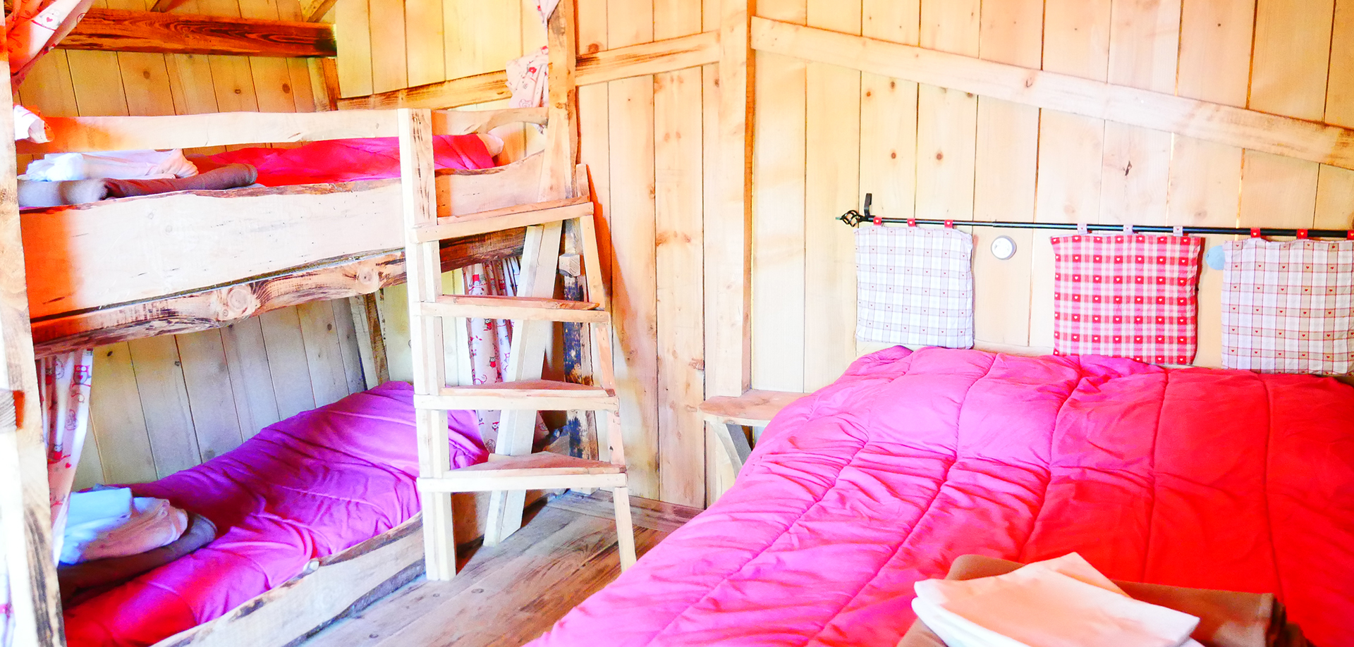 Inside of the Wooden Hut of Gretel with kitchen area, dinner place, double bed and bunk beds, rental of atypical cabins at the Campsite Les Castors in the Higher Rhine