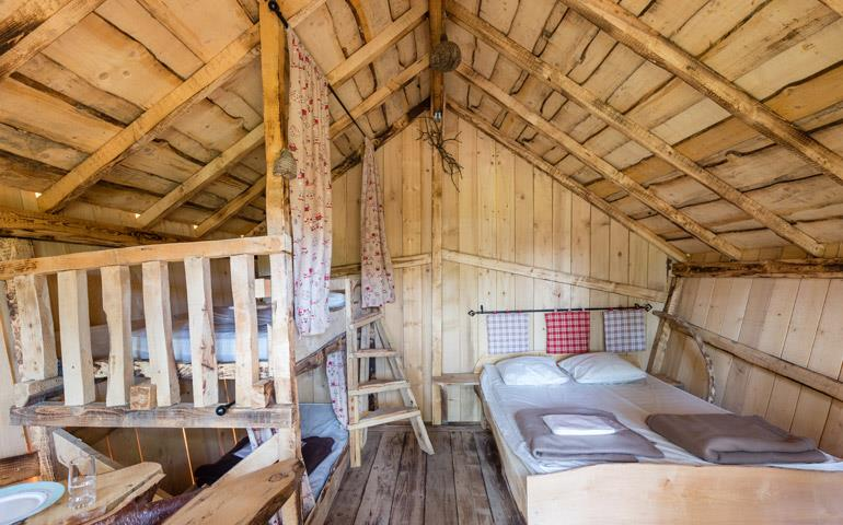 Double bed and bunk beds of the Wooden Hut of Gretel, rental of atypical cabins near the Vosges Mountains at the Campsite Les Castors