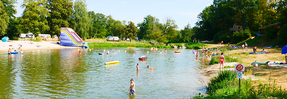 Natural summing lake with water slides and inflatable games at the campsite Les Castors, holiday rentals in Alsace